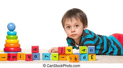 Little boy near blocks with alphabet