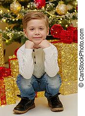 Little boy near the Christmas tree.