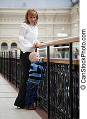 Little boy near to mum costs at fencing and having put hands on handrail looks in distance.