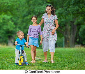 Little boy on a bicycle and his mother and sister