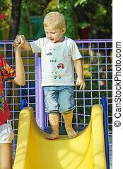 Little boy on a children's slide