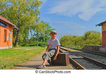 Little boy on a railway station, waiting for the train with vintage suitcase. Traveling, holiday and chilhood concept. Travel insurance concept. Travel, tourism, summer vacation and family concept