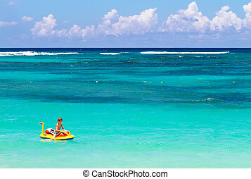 Little boy on an inflatable boat on a beautiful tropical beach