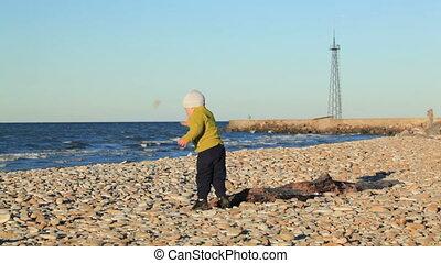 Little boy on pebble beach. - Little boy on pebble beach...