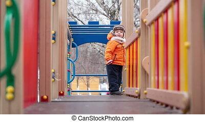 Little boy on playground equipment
