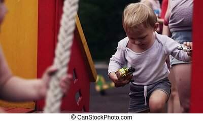 Little boy on playground play with toy. Mother with baby. Childhood. Family