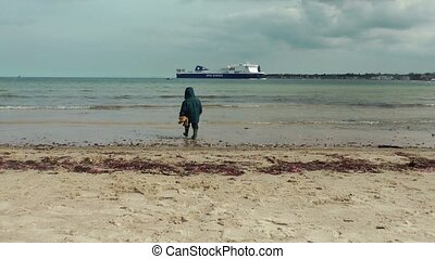 Little boy on polluted beach - Little boy playing on...