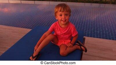 Little boy on poolside in sunset