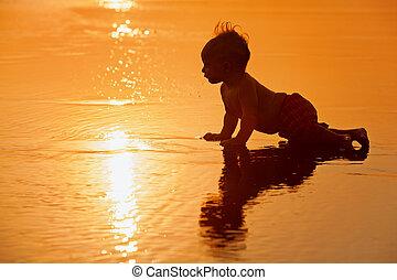 Little boy on sunset sea beach