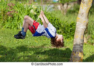 Little boy on swing - Little boy having a ball on a swing in...