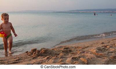 Little boy on the beach at sunset