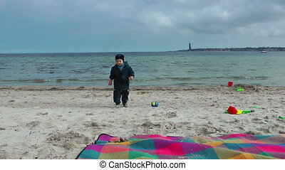 Little boy on the beach throwing stones into sea