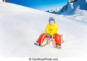 Little boy on the sledge slide down hill