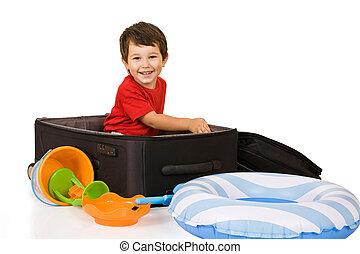 Little boy packs a suitcase