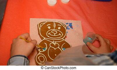 Little boy painting gingerbread teddy bear