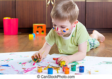 Little boy painting with colorful paints