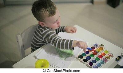 Little boy paints paints on table