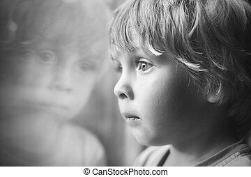 Little boy looking through window.