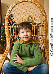 Little boy - Portrait of boy sitting in wicker chair and...