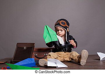 little boy pilot plays in the paper plane
