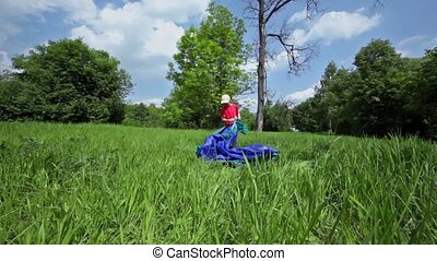 Little boy pitches tent on grass glade under blue sky