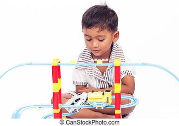 little boy play train toy