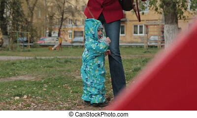 Little boy play with her mother with toy car in the park
