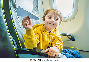Little boy play with paper plane in the commercial jet airplane flying on vacation