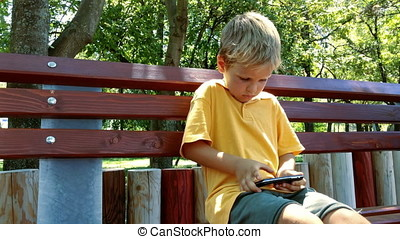 Little boy playing a game on mobile phone in the park