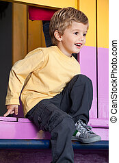 Cute little boy looking away while playing at playhouse