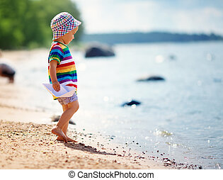 little boy playing at the beach in hat