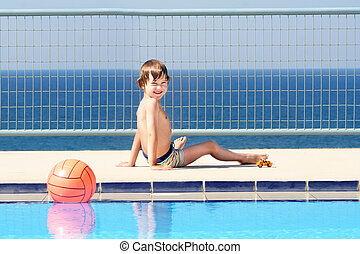 Little boy playing at the swimming pool