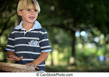 Little boy playing bongo in park