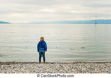 Little boy playing by the lake on a cloudy day