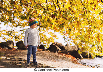 Little boy playing by the lake on a sunny day, wearing warm hat, grey knitted pullover, trousers and shoes