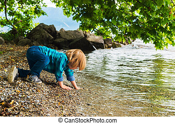 Little boy playing by the lake