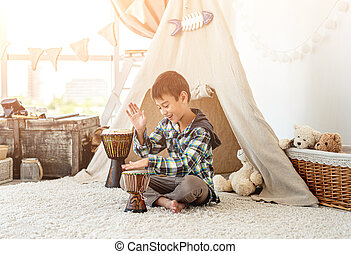 Little boy playing djembe drums indoors on wigwam background