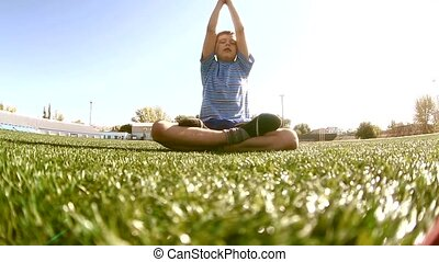 little boy playing doing yoga sports in a stadium a healthy...