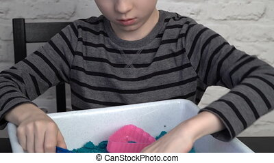Little boy playing with the molding sand at home