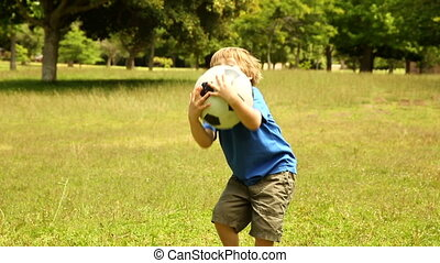 Little boy playing football at home in the garden