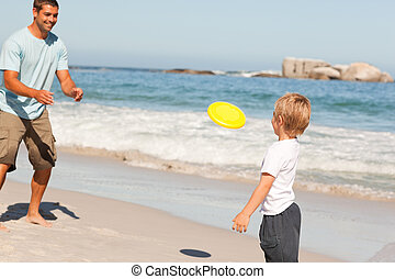 Little boy playing frisbee with his father