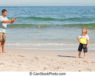 Little boy playing frisbee with his