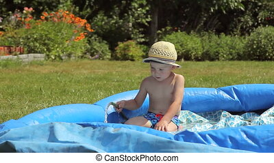Little boy playing in a pool in the garden