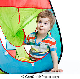 little boy playing in a tent