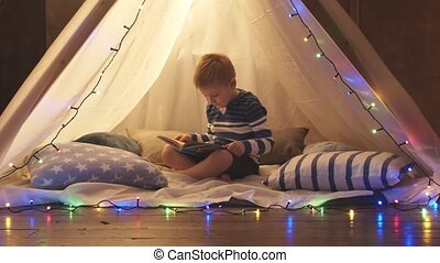 Little boy playing and reading a fairy tale in children's tent at home in the evening. Happy caucasian kid in the playroom.