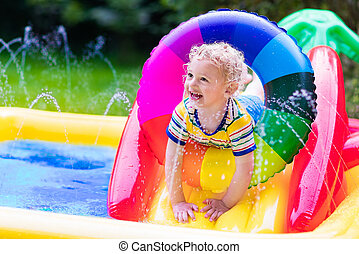 Little boy playing in garden swimming pool