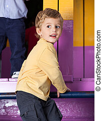 Cute little boy looking away while playing in kindergarten