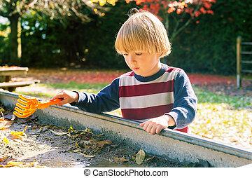 Little boy playing in muddy sandbox