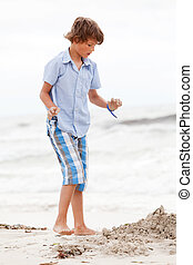 little boy playing in sand on the beach