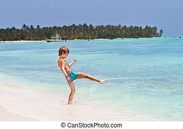 Little boy playing in the ocean on a tropical beach